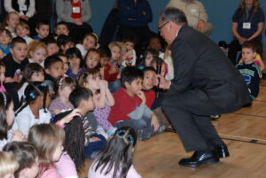 This is a colour photograph of Steven Point kneeling down to speak with a group of elementary school students in 2011.
