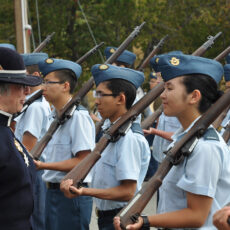 This is a colour photograph showing Judith Guichon in the Lieutenant-Governor uniform in front of youth at the Albert Head Air Cadet Summer Training Centre in 2013.