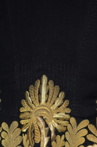 This is a close-up photograph showing detail on the Lieutenant-Governor uniform and the Conservator's stitches.