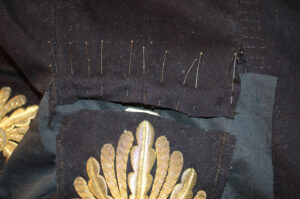 This is a photograph of pins holding pieces of the uniform together during the conservation process.