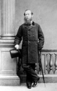 This is a black and white photograph of Joseph Trutch, standing, holding a top hat in one hand.