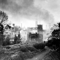 This is a black and white photograph of Government House on fire in 1957, smoke surrounds the building.