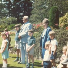 This is a colour photograph of Robert Rogers outside on a sunny day at a children's garden party in 1984, surrounded by children.