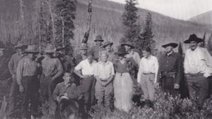 This is a black and white photograph, mountains in the background, showing Mary Gibson Henry, her husband, four children and some of the 1931 expedition crew.