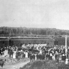 This is a black and white photograph of a large crowd of people outside a train full of soldiers leaving for World War I.
