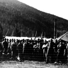 This is a black and white photograph of German prisoners of war outdoors, behind a fence near Vernon, BC.