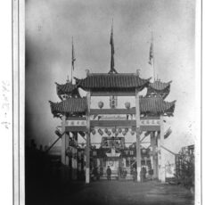 This is a black and white photograph of a Chinese arch on Store Street in Victoria, BC with people standing beneath it.
