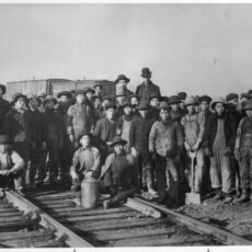This is a black and white photograph of a large group of Chinese railway workers posing on a railway track.