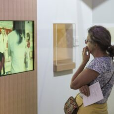 This is a photograph of a woman standing up and watching a video in the Our Living Languages exhibition.