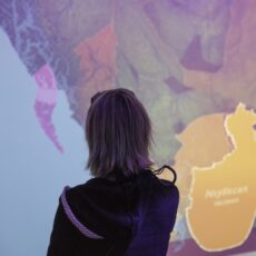 This is a photograph of a woman standing in front of and studying the First Peoples' Language map.