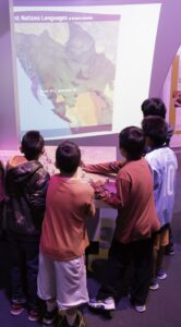 This is a photograph of five young boys gathered around the interactive First Peoples language map.