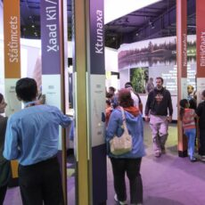 This is a photograph of visitors listening to greetings in the Welcome Forest of the Our Living Languages exhibition.