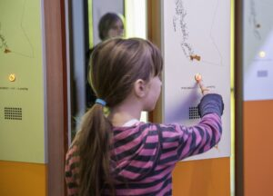 This is a photograph of a girl pressing a button on one of the welcoming panels at the Our Living Languages exhibition.