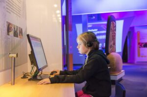 This is a photograph showing the profile of a child with headphones on sitting at a computer kiosk at the Our Living Languages exhibition.