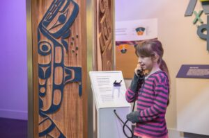 This is a photograph of a girl holding a receiver at the Interactive Light Pillar at the Our Living Languages exhibition.