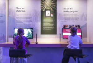 This is a photograph showing the backs of two children sitting at chairs, with headphones, using two separate computer kiosks at the Our Living Languages exhibition.