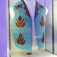 This is a photograph of a First Nations turquoise with red and black, beaded vest