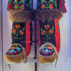 This is a photograph of high-topped First Nations moccasins with intricate beadwork and fur trim.