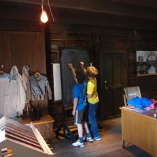 This is a photograph of two boys writing on a chalk board inside St Ann's Schoolhouse during a museum school program.
