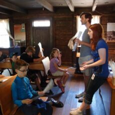 This is a photograph of museum staff standing and children at desks inside St Ann's Schoolhouse.