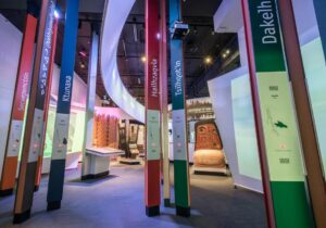 This is a photograph showing the tall, colourful language poles in the welcome forest at the Our Living Languages exhibition.