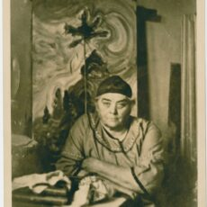 This is an image of Emily Carr taken in 1936, in her studio with one of her paintings in the background.