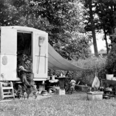 """This is a black and white photograph showing Emily Carr sitting on the steps of the trailer she named """"The Elephant."""
