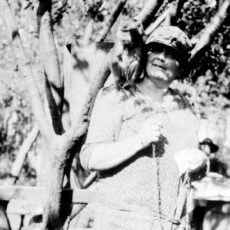 This is a black and white photograph of the artist Emily Carr with her pet monkey Woo on her right shoulder.