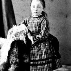 This is a black and white portrait of Emily Carr as a child at about age four or five. She is wearing a dress and standing next to a chair.