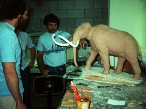 This is a photograph of museum staff creating a plasticine model of a Woolly mammoth.