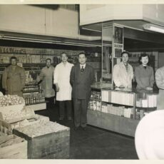 Inside the Yee Lun Ark Kee store, owner Wah Quan poses with his two brothers, his daughter, Reta Der, and three employees. Victoria, ca. 1951.
