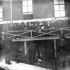 A Chinese witness taking the 'chicken oath' before the judge and jury on a platform outside the New Westminster courthouse; October 26, 1902.
