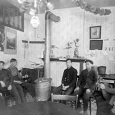 Tenants pose in the sitting room of a rooming house in Vancouver's Chinatown ca. 1902.