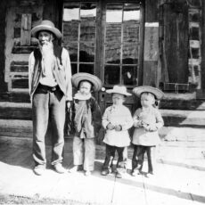 Nam Sing, one of the first Chinese miners to come to the Cariboo, seen standing with three children. There were very few Chinese children in the Cariboo during the time.