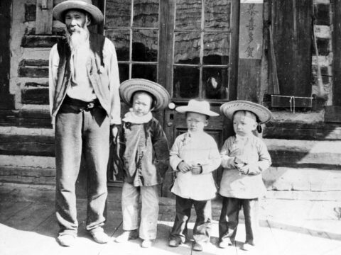 Nam Sing, one of the first Chinese miners to come to the Cariboo, seen standing with three children.