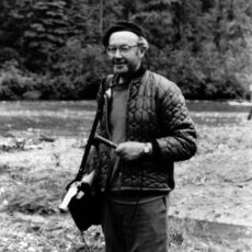Black and white photograph of Imbert Orchard, a CBC radio producer and oral historian. He is standing in a clearing of a wooded area, microphone in hand and recording equipment slung over his shoulder.