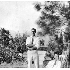 Black and white photograph of Paddy Acland as a young, handsome man. He is standing with arms crossed and is wearing light coloured slacks, a white dress shirt with the sleeves rolled up, and a dark coloured tie. He is standing in a wooded field. There is an unknown young man in shirt and tie sitting on a lawn chair in the bottom right hand side of the photograph.