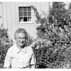 Black and white photograph of Dora Kloss standing at the side of her house. Behind her is a lush garden. Mrs. Kloss is an older woman with short grey hair. She is wearing a simple collared, short-sleeved, button-up dress.