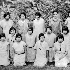 This is a photograph of a class of young Aboriginal girls. They are located outside and are standing in three lines, with some kneeling on the ground. There are non-Aboriginal teachers standing on either side of the group. All the girls are wearing European-style dresses and have short hair.