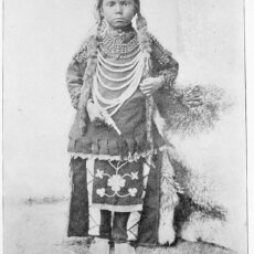 A black and white photograph of a young Aboriginal boy, Thomas Moore, before he went to the Regina Indian Industrial School. He is in traditional Cree clothing and his hair is in two long braids.