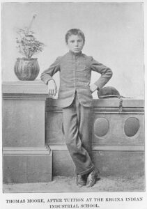 A black and white photograph of a young boy, Thomas Moore, after arriving at the Regina Indian Industrial School in Saskatchewan. He no longer has his long braids, rather a European style haircut, and he is in his school uniform which resembles a European uniform.