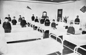 A black and white photo of the younger boys' dormitory at the Coqualeetza Residential School. There are 14 Aboriginal boys in the image and 15 beds; however, this image only shows a portion of the whole room. The boys, wearing their uniforms, are standing beside the beds.
