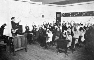 A black and white photograph of a female teacher giving a lesson to approximately 20 Aboriginal children. She is holding up a card at the front of the classroom and all the children are also holding up a card.