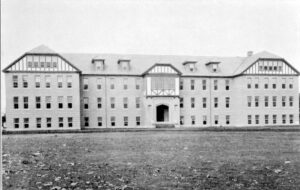 A black and white photograph of the exterior of the Coqualeetza Residential School. It is a large four-storey building located in a vast clearing.