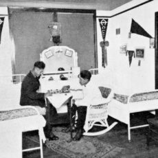 A black and white photograph of two young Aboriginal men playing checkers in their dormitory. There are only two beds in their room. They are dressed in their European-style uniforms.