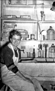 Stanley Fox seated wearing an apron in a photography darkroom.
