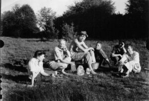 Six young people seated on a grassy field, trees in the background. One has cream on his face from a scene from the film they are making together.