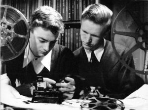 Stanley Fox and his co-director Peter Varley. Fox is holding a piece of film and both are looking at a frame, determining whether they should include it in their film. The two young men are sitting between two film reels mounted on winders.