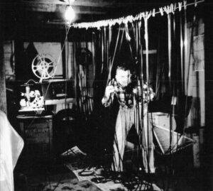 Stanley Fox editing film in the 1960s. Long strips of 16mm film are hanging from clotheslines inside a small darkroom. There are newspapers scattered all over the floor and Fox is peering through the curtain of filmstrips. A film projector sits on a wooden box on the left side.