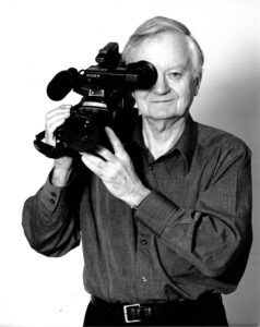 Stanley Fox poses with a large film camera propped on his right shoulder. He is wearing a collared shirt and black pants.